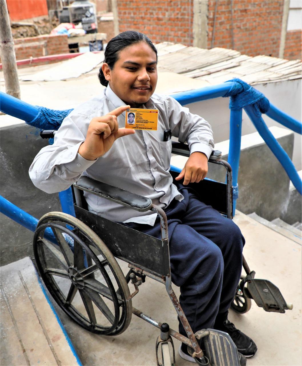 Persona con discapacidad en silla de ruedas mostrando su carnet amarillo del CONADIS