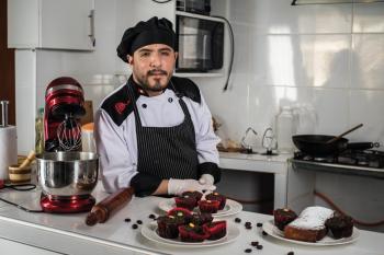 estudiante del ceptro vestido con madil y gorro junto a sus productos de pastelería