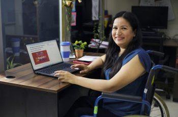 mujer usuaria de silla de ruedas usando una computadora con la página web del registro nacional del conadis